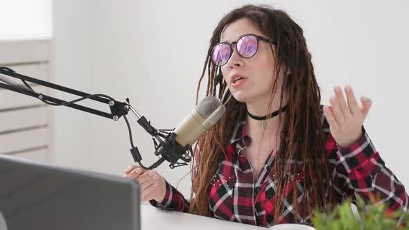 Thumbnail for Concept of Streaming and Broadcasting. Young Cheerful Girl in the Studio Speaks Into a Microphone