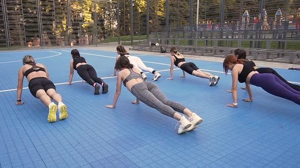 Thumbnail for Young Slim Ladies in Sportswear Doing Plank on the Sportground in the Park