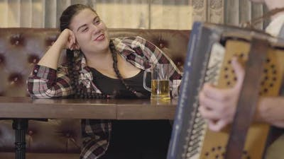 Unrecognizable Man Playing the Accordion While Attractive Plump Woman Drinking Beer and Sending Him