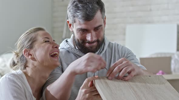 Thumbnail for Woman Helping Man Assembling Shelf