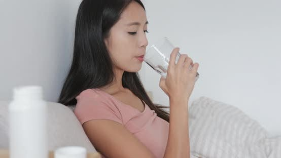 Thumbnail for Woman taking pills and drinking glass of water