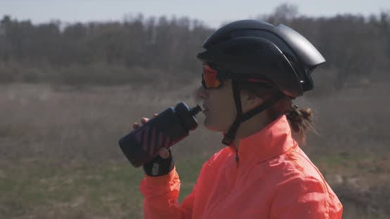 Portrait of woman cyclist in helmet and sunglasses is drinking water from bottle. Cycling hydration