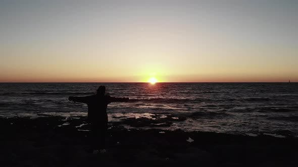 Silhouette of Young Woman Standing on The Rocky Beach with Hands Spread to Sides on Sunset at Sea