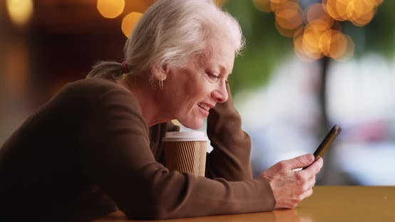 Thumbnail for Cheerful senior woman texting on phone in outdoor setting smiling and laughing
