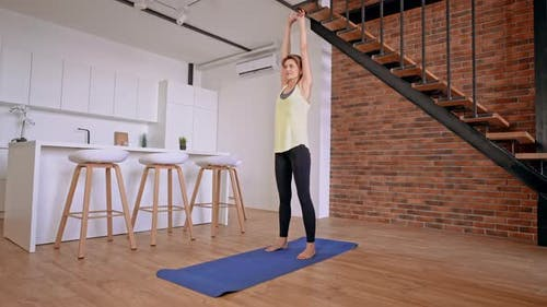 Slim Female Stretching in Apartment