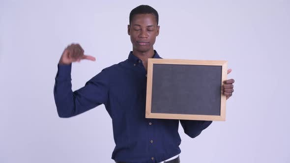 Thumbnail for Young Stressed African Businessman Holding Blackboard and Giving Thumbs Down