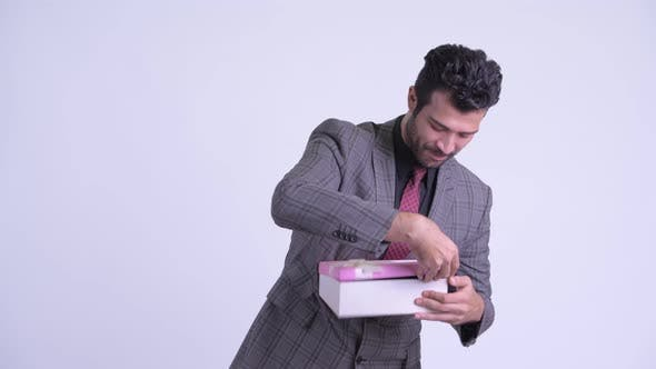 Thumbnail for Happy Bearded Persian Businessman Opening Gift Box