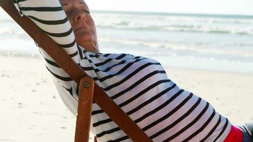 Senior woman relaxing on sunlounger at beach