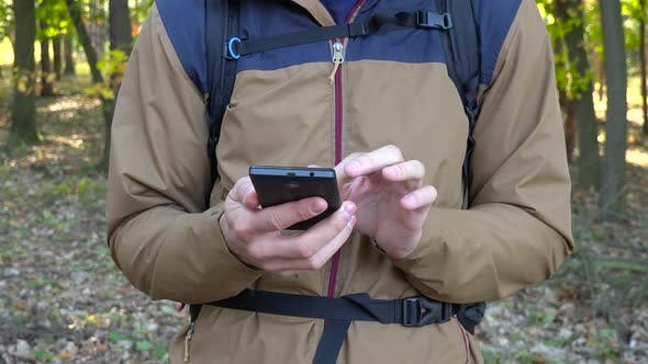 Thumbnail for A Backpacker Works on a Smartphone in a Forest - Closeup
