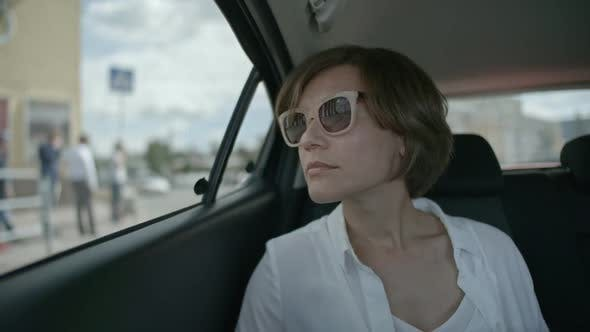 Cover Image for Business Lady Riding on Backseat and Looking through Car Window