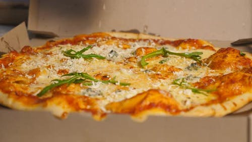 Male Hand of Chef in Glove Finishing Tasty Vegetarian Pizza with a Sprinkles Grated Parmesan at