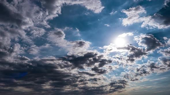 Dramatic Cumulus Cirrus Clouds Move in the Blue Sky. Sunbeams Shine. Time Lapse