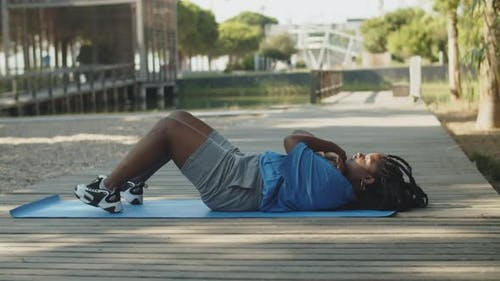 Long Shot of Fat American Woman Doing Abdominal Crunches Outdoor