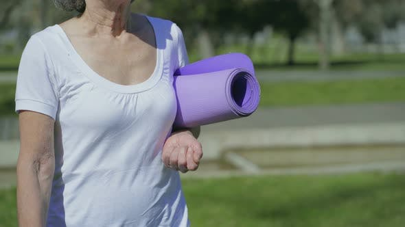 Thumbnail for Middle-aged Female Body Walking in Park with Yoga Mat in Hand