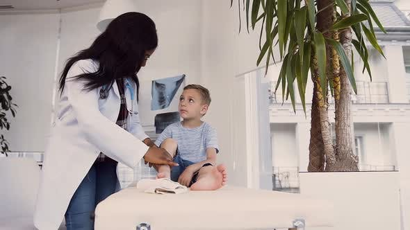 Thumbnail for Doctor Inspecting Injured Leg of the Little Boy
