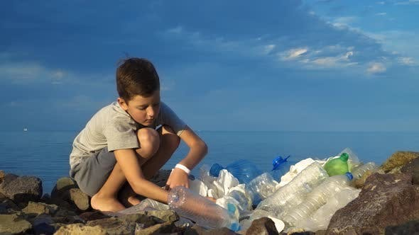 Thumbnail for Little Child Volunteer Cleaning Up the Beach at the Ocean. Safe Ecology Concept