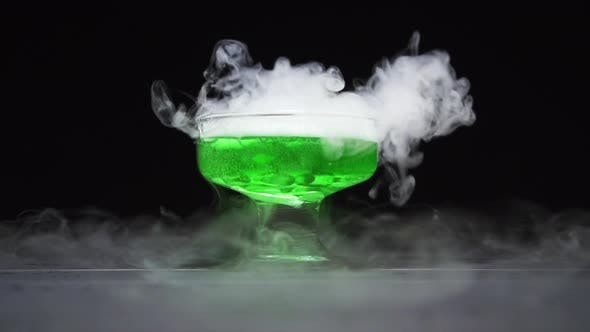 Thumbnail for Green Liquid Boils Giving Off Smoke in a Glass Bowl on a Black Background
