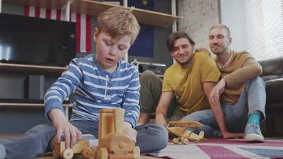 Boy with Two Fathers Playing with Toys