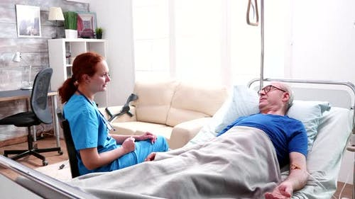 Female Doctor Talking Old Man Lying in Bed in a Nursing Home
