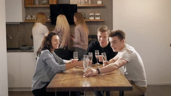 Young People Sitting at Table with Food and Drinks