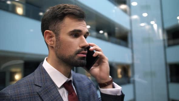 Businessman Talking on Cellphone in Hotel Lift