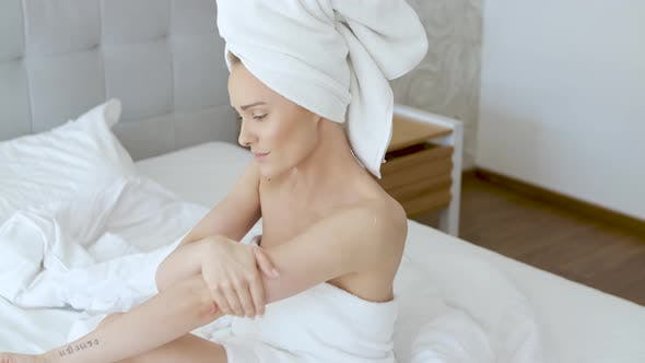 Thumbnail for Middle Aged Beautiful Blond Woman Moisturizes Legs After the Shower