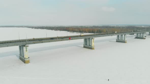 Thumbnail for Cars Drive Along Long Bridge Over Frozen River on Sunny Day
