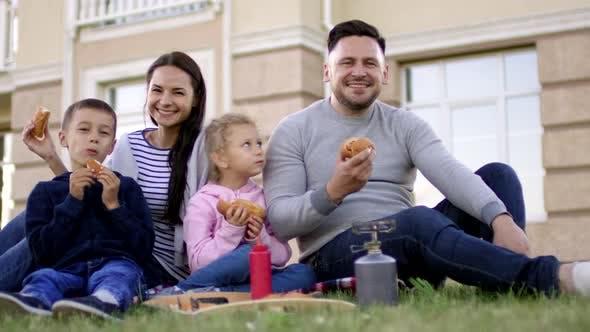 Happy Caucasian Family Enjoying Hotdogs on Lawn