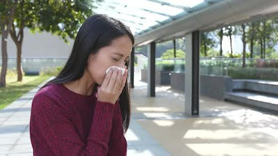 Woman sneeze at outdoor
