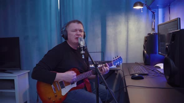 Thumbnail for Male Musician With Instrument Guitar Records Songs In Home Sound Studio