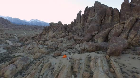 Thumbnail for Aerial shot of a young man backpacker camping with his dog in a mountainous desert