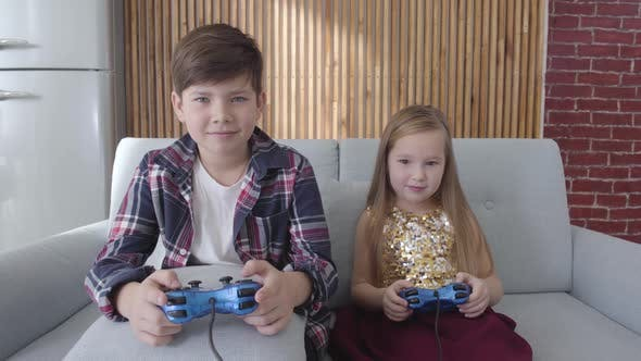 Two Caucasian Children Playing Video Game As Sitting on Couch at Home. Boy and Girl Winning, Making