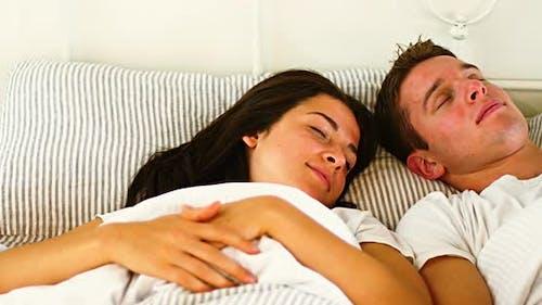 Couple sleeping in bedroom