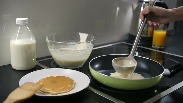 Hand Pouring Pancake Batter Into the Pan