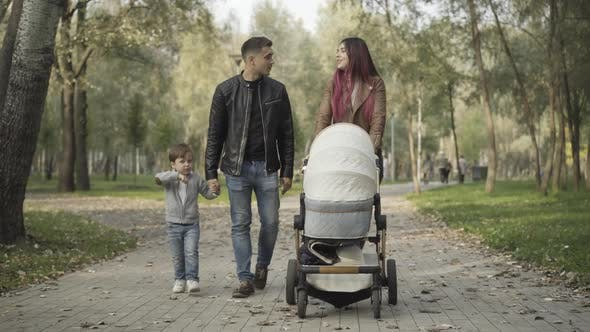 Thumbnail for Wide Shot Portrait of Happy Young Caucasian Family Strolling Along Park Alley and Talking