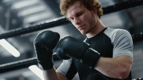 Focused Fighter Waiting for Fight in Sport Club. Kickboxer Wearing Boxing Gloves