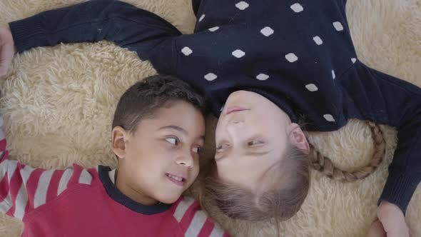 Thumbnail for Portrait Cute African American Boy and Blond Caucasian Girl Lying on the Floor on the Beige Fluffy