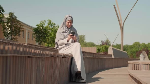 Thumbnail for Muslim Woman Using Cellphone Outdoors