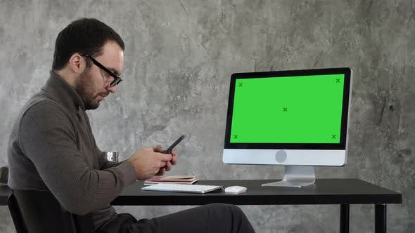 Thumbnail for Businessman Looking at His Smartphone Messaging and Sitting Near Computer Screen. Green Screen Mock