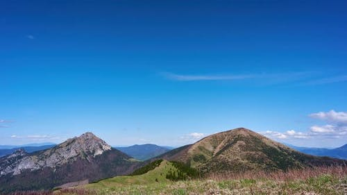 Mountain peaks in the national park, blue sky with hilly clouds in the background