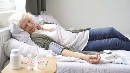 Woman of Retirement Age Is Lying on a Bed with a Blood Pressure Monitor on Her Arm Her Blood