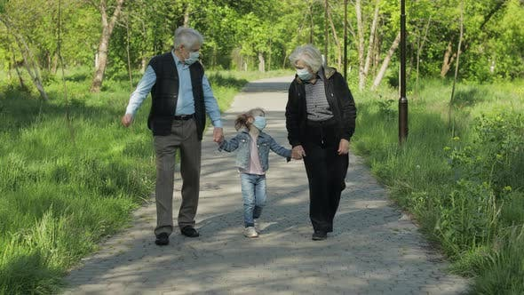 Grandparents with Granddaughter Takes Off Masks After Coronavirus Quarantine End