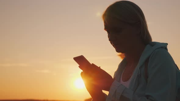 Thumbnail for Silhouette of a Middle-aged Woman Using a Smartphone at Sunset