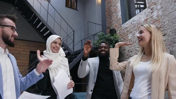 Cover Image for Young International People Greeting Each other with High Five Before the Beginning of Work
