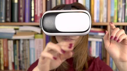 Young Woman in VR Glasses in the Library. A Woman with a VR Helmet on Her Head Examines and Touches