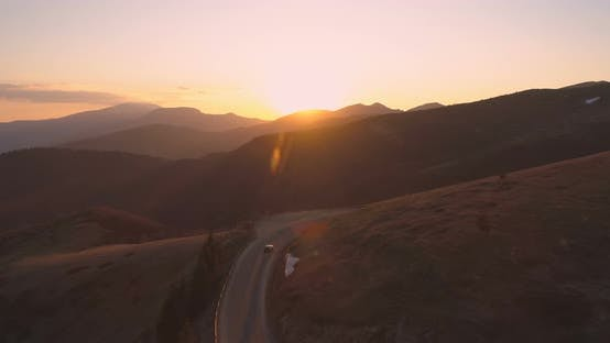 Drone Following Lonely Car Driving on Curved Mountain Road Reflecting the Sunset Lights
