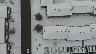 Aerial view over snow covered city street and houses in snow winter road covered