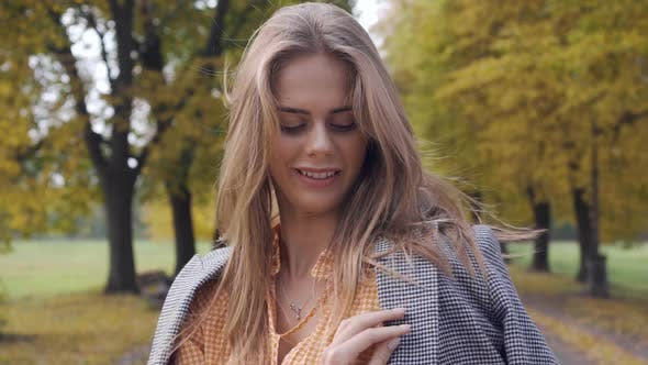 Thumbnail for Smiling Caucasian Girl Putting on Checkered Jacket and Looking Away