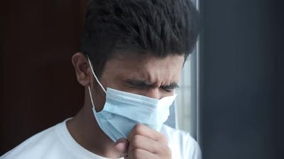 Young Sick Man in Face Mask Coughing and Sneezes Indoor