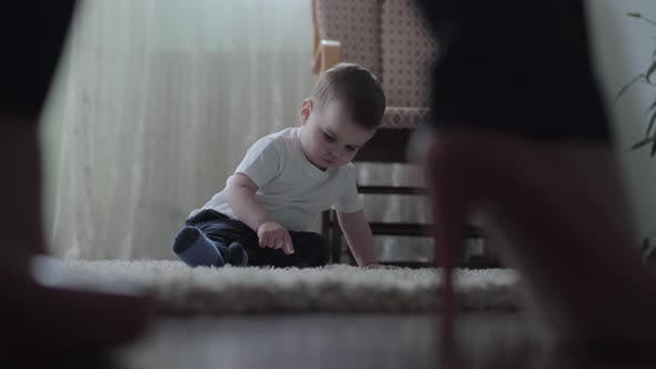Cover Image for Cute Baby Boy Sitting on the Floor on Fluffy Carpet Playing Alone While His Young Mother Walking in